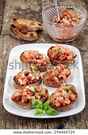 plate of bruschettas on wooden table - stock photo