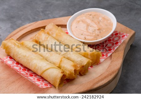 Plate of cheese sambusek,traditional Arabic food / Cheese rolls plate with cocktail sauce served in a wooden plate on a rustic background - stock photo