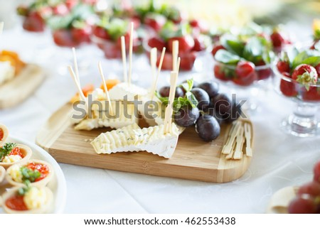 Plate of Cheese with grape on wooden plate at a restaurant