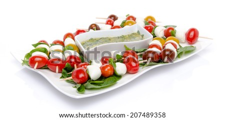 Plate of cherry tomatoes and mozzarella on skewers and a vinaigrette sauce with basil, isolated on white - stock photo
