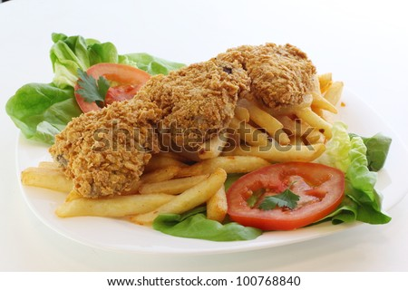 Plate of chicken drumstick on french fries - stock photo