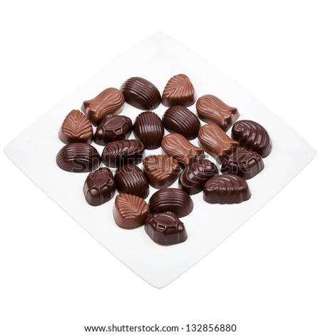 Plate of chocolates isolated on white background - stock photo