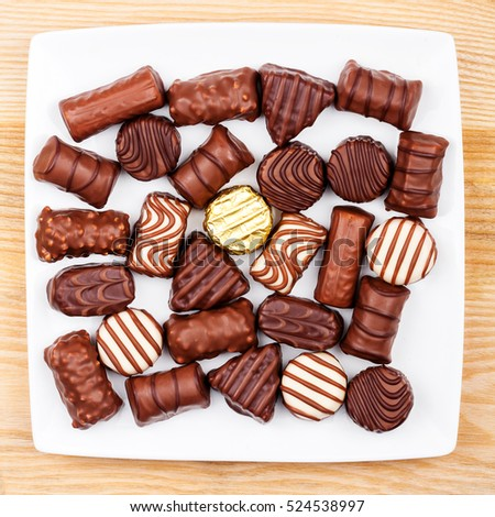 Plate of chocolates on a wooden surface