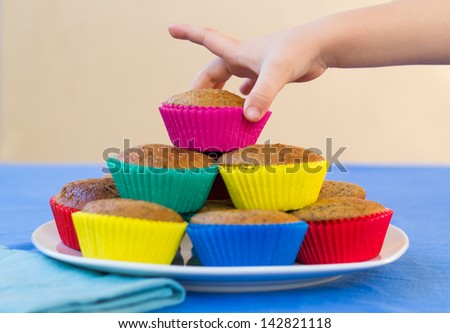 Plate of colourful, home-made muffins for a children's party, with a child's hand reaching for a muffin. - stock photo