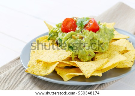 plate of corn tortilla chips with guacamole dip on beige place mat - close up