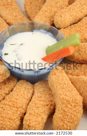plate of crispy chicken fingers with  vegetables and dip - stock photo