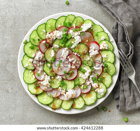 Plate of cucumber and radish salad with green onions and fresh cheese, top view - stock photo
