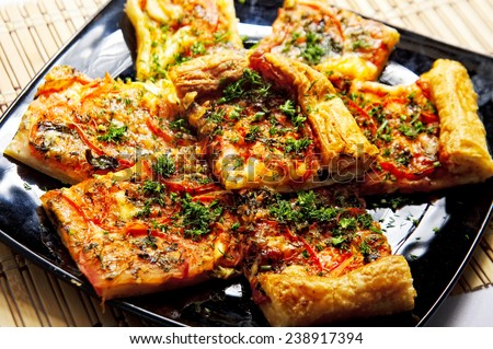 Plate of cut pizza pieces topped with dill - stock photo