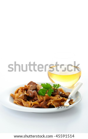 Plate of delicious beef stroganoff with wine. - stock photo