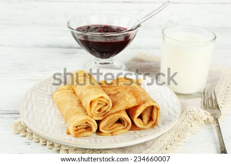 Plate of delicious pancakes and berry jam in glass bowl, glass of milk on wooden background