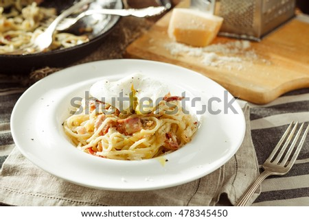 Plate of delicious spaghetti Carbonara with poached egg. Italian food. Rustic styled