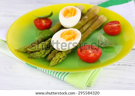 Plate of dietary salad with boiled asparagus and egg, closeup - stock photo