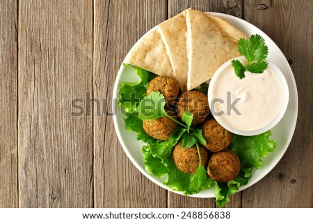 Plate of falafel with pita bread and tzatziki sauce on wooden table. View from above - stock photo