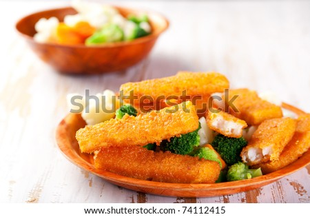 Plate of fish fingers with vegetables side dish - stock photo