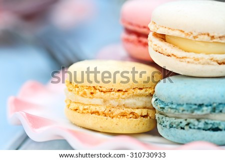 Plate of fresh colorful macarons. Extreme shallow depth of field with selective focus on yellow lemon macaron.