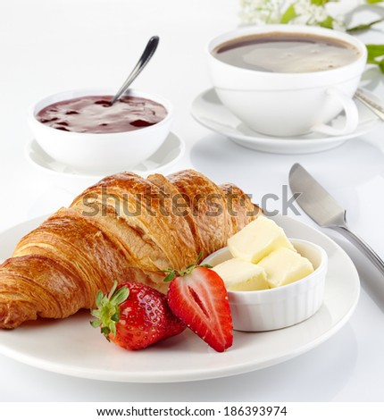 Plate of fresh croissant and cup of coffee on white background - stock photo