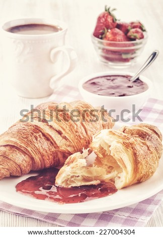 Plate of fresh croissants and jam, cup of coffee and strawberries with retro vintage filter effect - stock photo