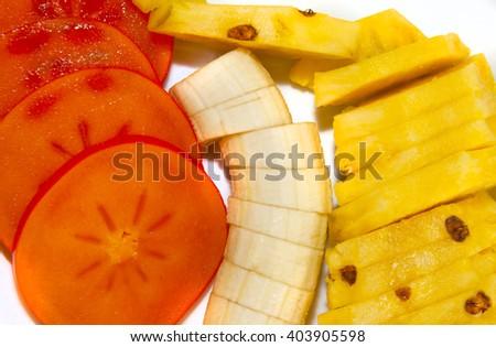 Plate of fresh fruits (kaki, banana and pineapple) sliced as a take away food - stock photo