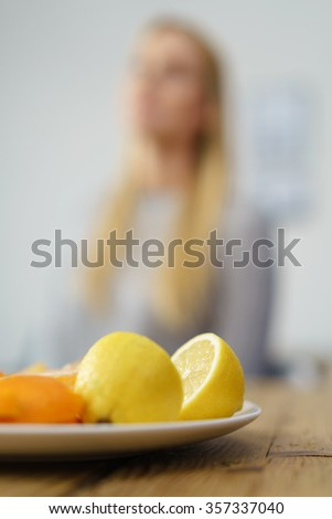 Plate of fresh halved lemons and oranges on a wooden dining table with a blurred seated woman in the background in a healthy diet and lifestyle concept - stock photo