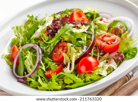 Plate of fresh salad with cherry tomatoes and onions - stock photo