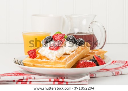 Plate of fresh waffles and berries with whipped cream and maple syrup. - stock photo