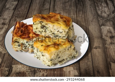 Plate of Freshly baked Serbian Traditional Zeljanica Spinach-cheese Pie slices, set on very old, weathered, cracked, scratched, peeled off, Wooden Table surface.