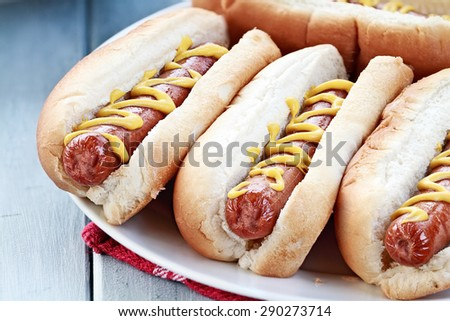 Plate of freshly grilled hotdogs with mustard. Extreme shallow depth of field. - stock photo