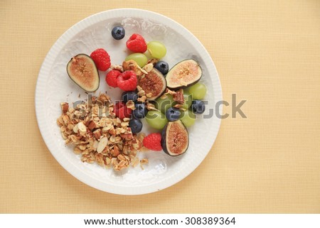 Plate of granola with figs, raspberries, blueberries and grapes, copy space included - stock photo