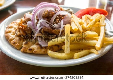 Plate of Greek lamb gyros with fries and onions. Greek speciality. - stock photo