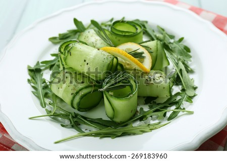 Plate of green salad with cucumber, arugula and rosemary, closeup