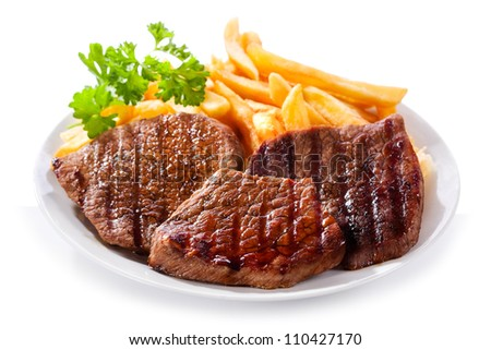 plate of grilled meat with fries on white background - stock photo