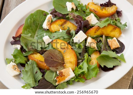 Plate of grilled peach and Mozzarella salad with mixed baby greens and balsamic vinegar in a rustic setting. - stock photo