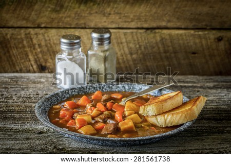 Plate of hearty beef stew on a rustic background. - stock photo