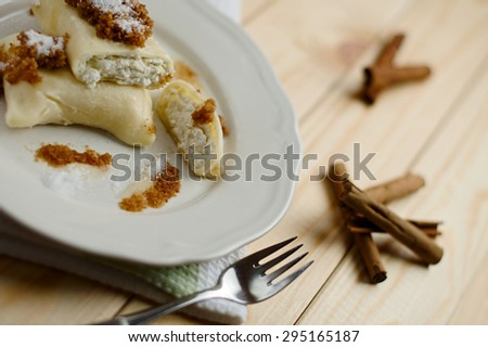 Plate of homemade sweet fresh cottage cheese filled dumpling roll, topped with butter roasted breadcrumbs with powdered cinnamon and granulated sugar. Traditional Slovenian cuisine. On a wooden table.