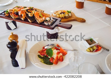 Plate of Italian Appetizer bruschettas on wooden desk on the table.Italian antipasti, jamon, prosciutto, chorizo, salami on a grunge black board, rustic style. Selective focus. - stock photo