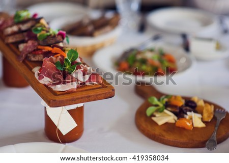 Plate of Italian Appetizer brusquets on wooden desk on the table.Italian antipasti, jamon, prosciutto, chorizo, salami on a grunge black board, rustic style. Selective focus. - stock photo