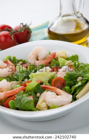 Plate of Italian shrimp salad with shrimp, tomatoes, artishocke hearts, Romane lettuce leaves, fava beans, and pine nuts. Olive oil.  - stock photo