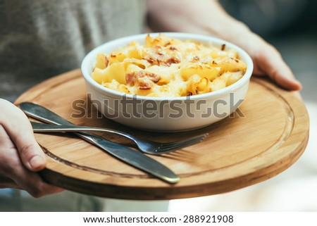 Plate of macaroni with cheese and bacon in hands. Toned picture - stock photo