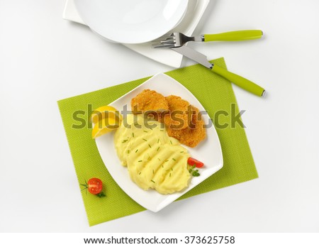 plate of mashed potato puree with chopped chives and breaded turkey breast on green place mat - stock photo