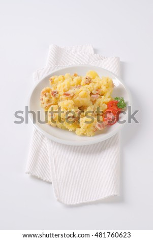 plate of mashed potatoes with bacon on white background
