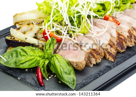 plate of meat and grilled vegetables on a white background