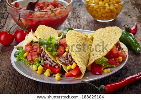 Plate of Mexican food Tacos on old wooden table - stock photo