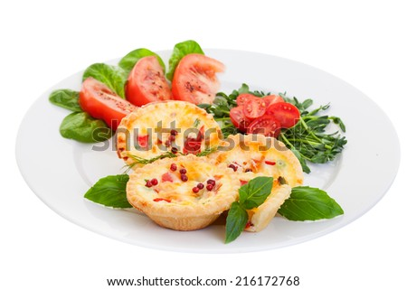 Plate of Mini quiche on a white background filled with vegetables with salad.Focus on the front pies. - stock photo