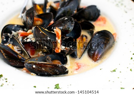 Plate of mussels in garlic sauce horizontal - stock photo