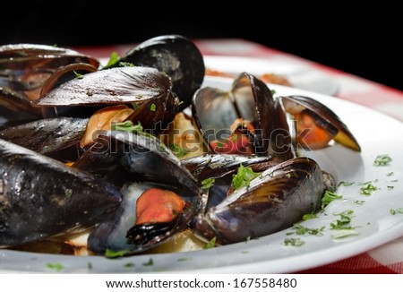 Plate of mussels with prawns in the background. Restaurant shot. - stock photo