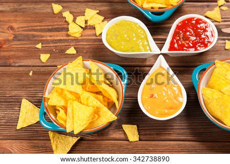 Plate of nachos with salsa, cheese and guacamole dips - stock photo