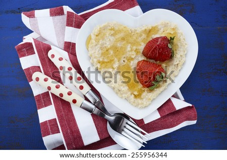 Plate of nutritious and healthy cooked breakfast oats with strawberries and honey in heart shaped bowl on dark blue rustic wood table. - stock photo