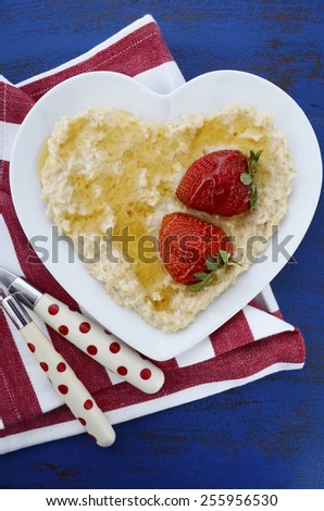 Plate of nutritious and healthy cooked breakfast oats with strawberries and honey in heart shaped bowl on dark blue rustic wood table, vertical. - stock photo