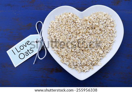Plate of nutritious and healthy oat flakes in heart shaped bowl on dark blue rustic wood table, with I Love Oats message tag. - stock photo