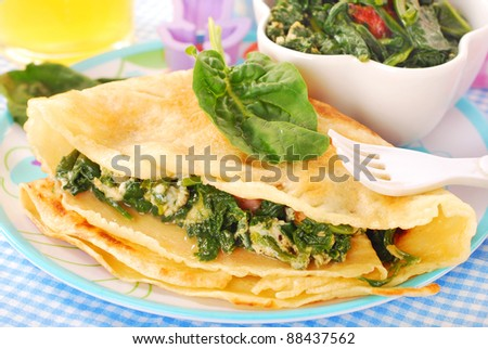 plate of pancake stuffed with spinach ,bacon and eggs for child - stock photo